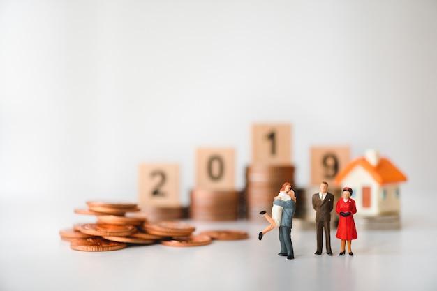 Gens miniatures, famille debout avec des pièces de pile et fond de l'année 2019