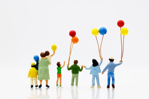 Les gens miniatures, la famille et les enfants s'amusent avec des ballons colorés.