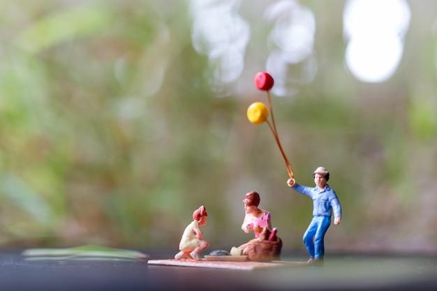 Gens miniatures: famille heureuse assis sur le tapis lors d'un pique-nique dans un parc