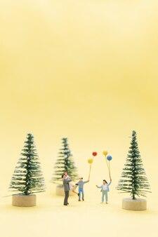 Gens miniatures, famille heureuse célébrant un concept de noël, noël et bonne année.