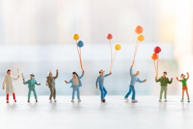 Gens miniatures: famille heureuse marchant avec des ballons