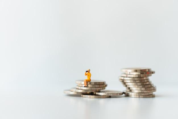 Gens miniatures, femme assise sur des pièces de pile en utilisant comme concept commercial et financier