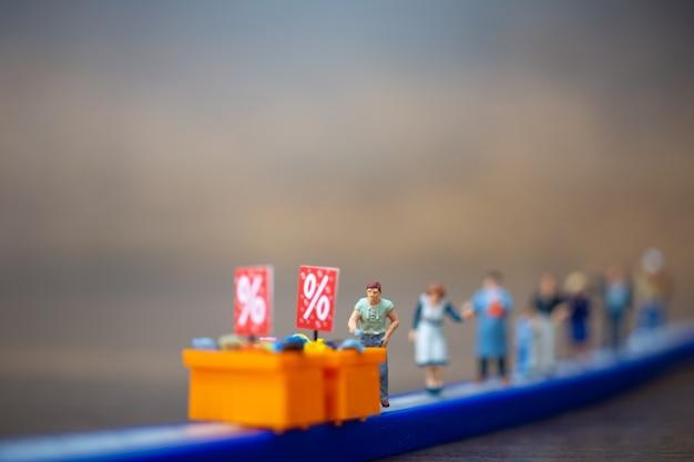 Les gens miniatures gardent la distance dans le centre commercial et la zone publique. concept de distanciation sociale.