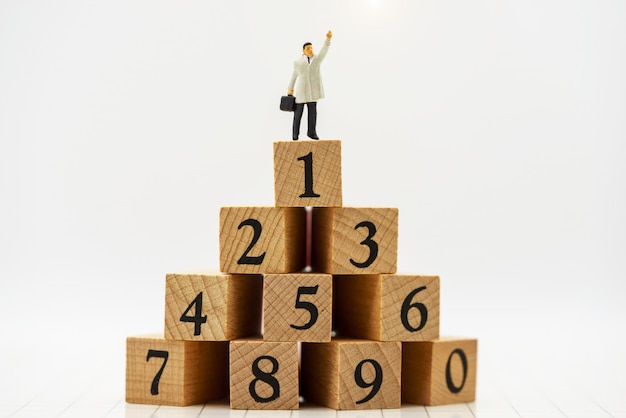 Gens miniatures: gens d'affaires debout sur une boîte en bois avec le haut du classement.