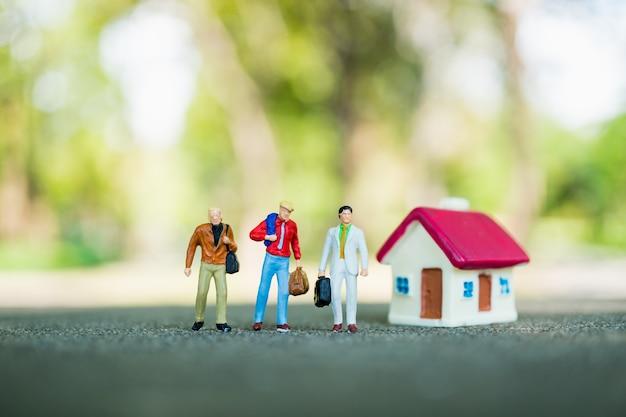 Gens miniatures, groupe d'homme d'affaires permanent avec mini maison sur fond de nature verte en utilisant comme