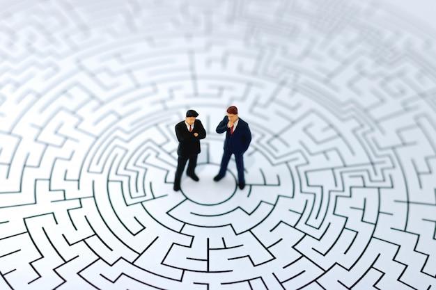 Gens miniatures: homme d'affaires, debout au centre du labyrinthe.