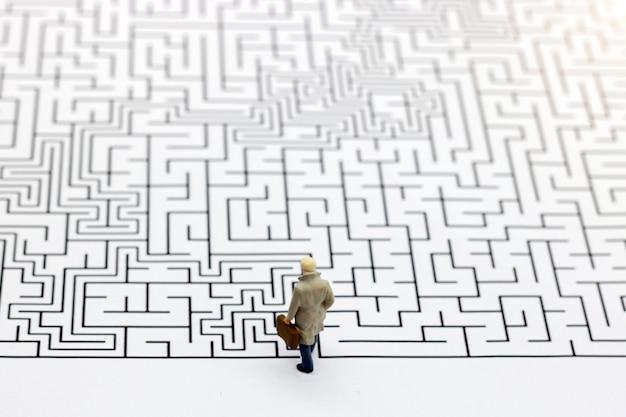 Gens miniatures: homme d'affaires debout au début du labyrinthe.