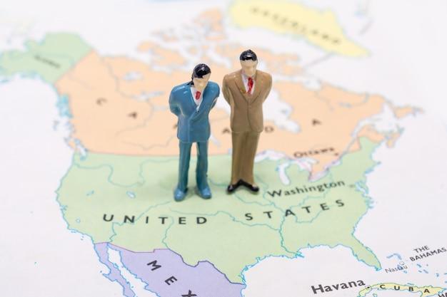 Gens miniatures, homme d'affaires debout sur la carte américaine