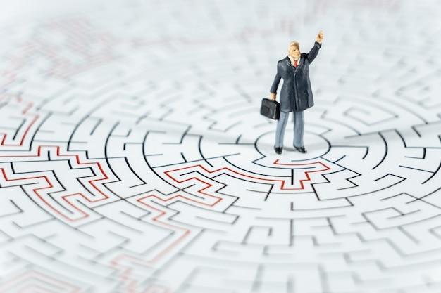 Gens miniatures homme d'affaires debout sur le centre du labyrinthe à l'aide