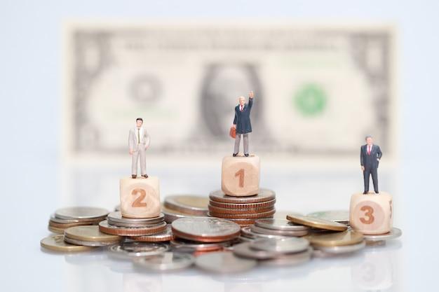 Gens miniatures: homme d'affaires debout sur des pièces empilées