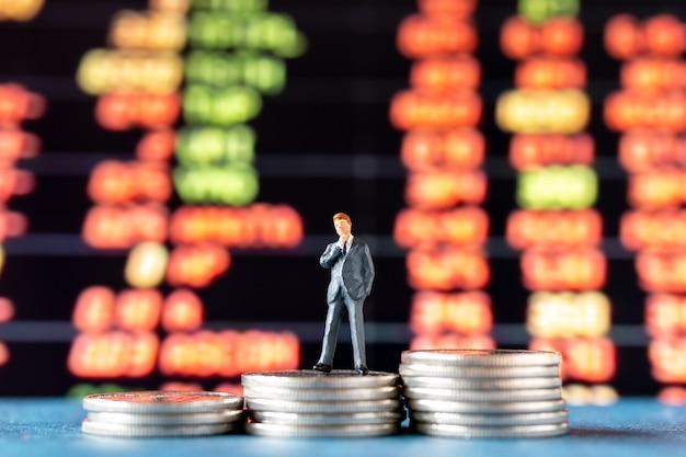 Gens miniatures, homme d'affaires debout sur une pile de pièces avec affichage graphique