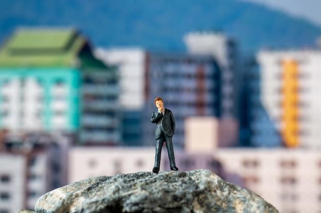 Gens miniatures, homme d'affaires debout sur le rocher avec bâtiment