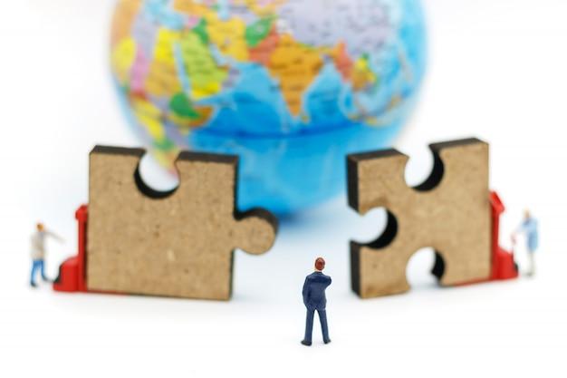 Les gens miniatures: l'homme d'affaires a l'idée de connecter un puzzle.