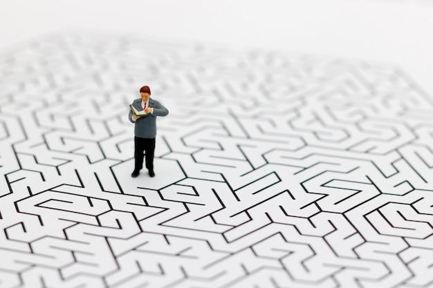 Gens miniatures: homme d'affaires lisant au centre du labyrinthe.