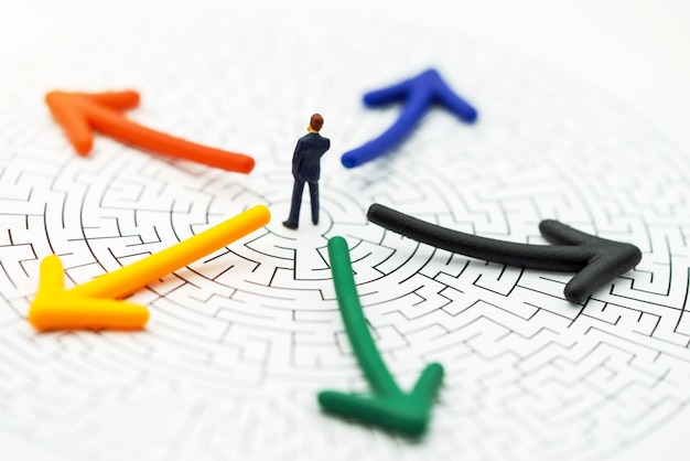 Gens miniatures, homme d'affaires pensant briser le mur dans un labyrinthe