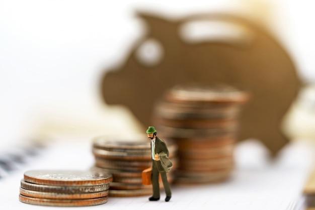 Gens miniatures: homme d'affaires avec pile de pièces et cochon en bois. concept de finance et d'investissement.