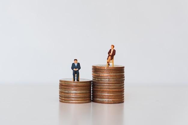 Gens miniatures, homme et femme assis sur des pièces de pile en tant que concept commercial et financier