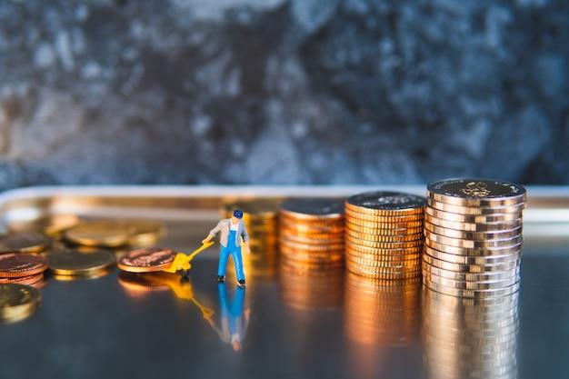 Les gens miniatures, l'homme tirant des pièces de pile à l'aide de concept logistique, commercial et financier