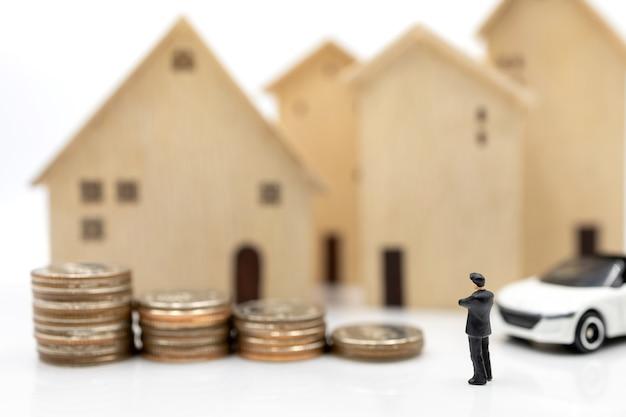 Gens miniatures: hommes d'affaires se serrant la main sur la pile de pièces avec maison et voiture. concept d'investissement dans le logement et les véhicules.
