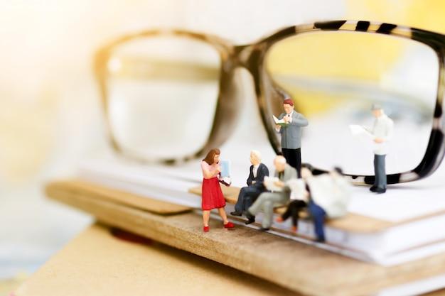 Gens miniatures lisant et assis sur un livre avec des lunettes.