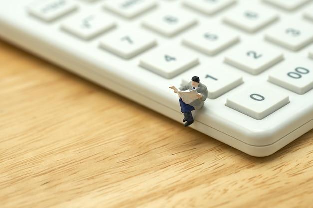 Les gens miniatures lisent journal assis sur la calculatrice blanche