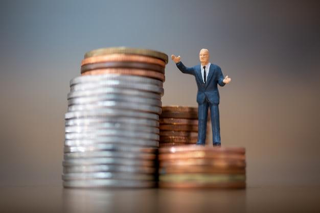 Gens miniatures: petits hommes d'affaires debout avec pile de pièces, concept de croissance d'entreprise.