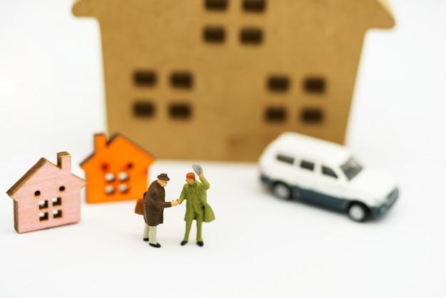 Gens miniatures: poignée d'hommes d'affaires devant un bloc en bois avec maison et voiture.