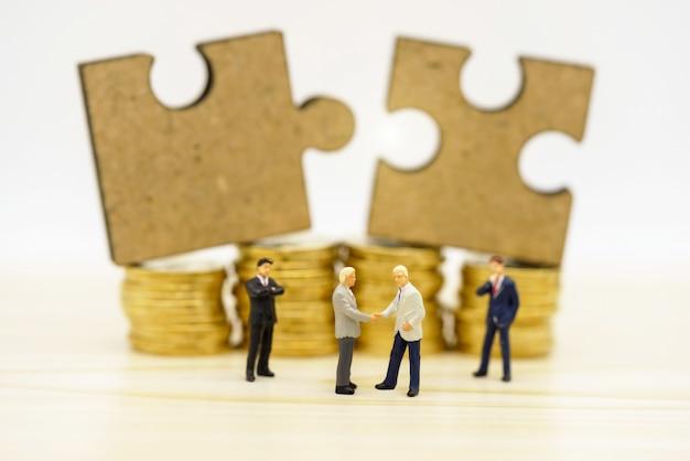 Gens miniatures: poignée d'hommes d'affaires avec un puzzle sur une pile de pièces. la finance .