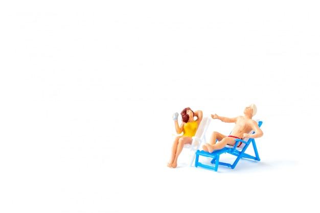 Les gens miniatures se faire bronzer sur des chaises longues, le concept de l'heure d'été