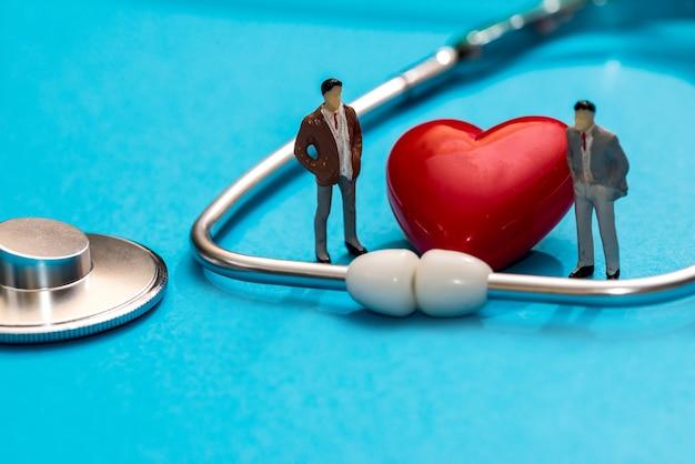 Gens miniatures avec stéthoscope, pilules et coeur isolé sur une surface bleue