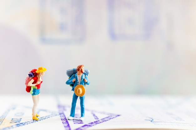 Gens miniatures: voyageur avec sac à dos marchant sur le passeport