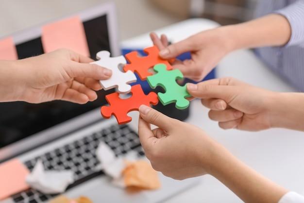 Les gens avec des morceaux de puzzle au bureau