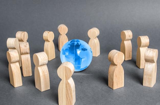 Les gens ont entouré un globe planète terre coopération et collaboration des gens du monde entier