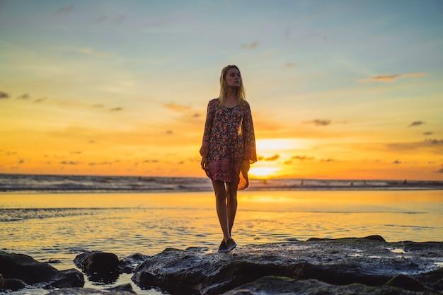 Les gens sur la plage au coucher du soleil. la fille saute sur le fond du soleil couchant.