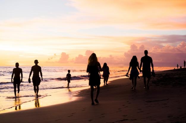 Les gens sur la plage au coucher du soleil.