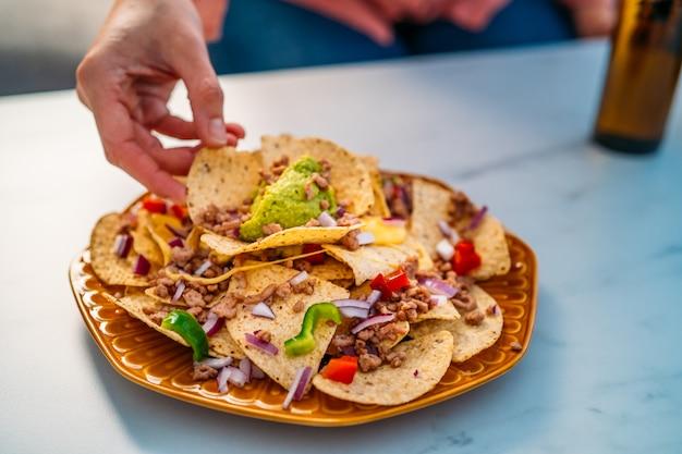 Les gens plongent les chips de nacho de maïs jaune garni de boeuf haché, de guacamole, de fromage fondu, de poivrons et de feuilles de coriandre en plaque sur une table en pierre blanche