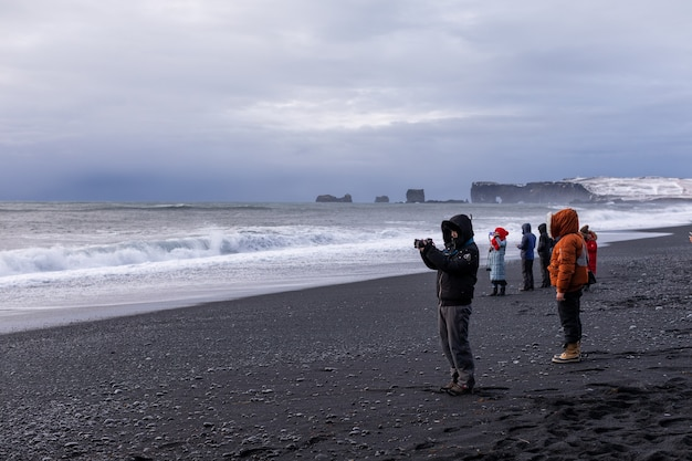 Les gens prennent des photos sur le panorama et les vagues de l'océan atlantique d'hiver et de la plage de reynisfjara choni