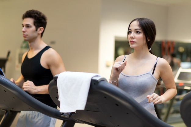 Les gens qui courent sur le tapis roulant dans une salle de sport