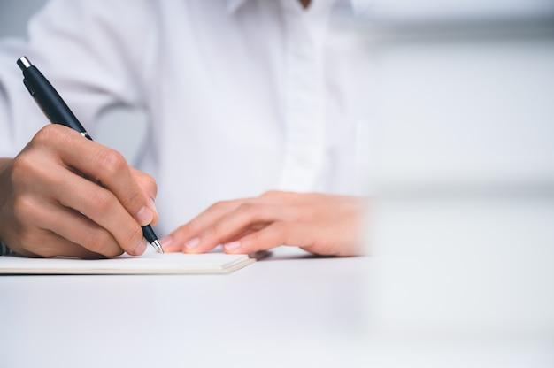 Les gens qui écrivent sur un ordinateur portable et travaillent avec du papier sur une table en bois.