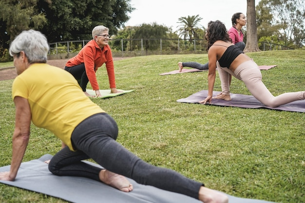 Les gens qui font des cours de yoga tout en gardant une distance sociale au parc de la ville