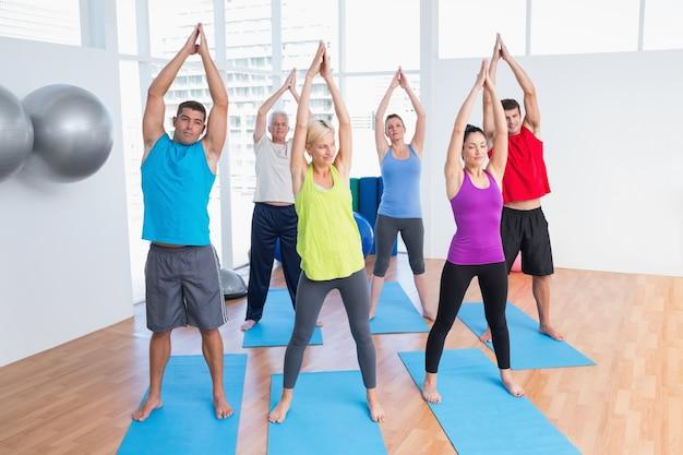 Gens qui font des exercices d'étirement dans un cours de yoga