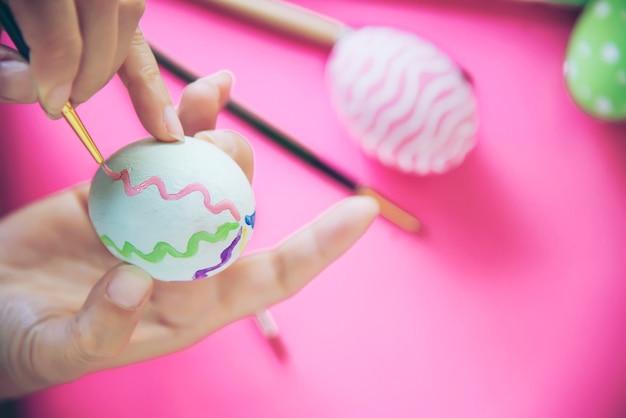 Gens qui peignent des oeufs de pâques colorés - concept de célébration de vacances de pâques