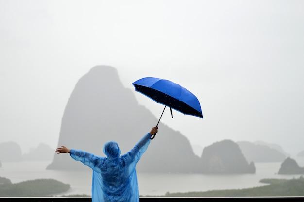 Les gens qui portent des imperméables et des parapluies bleus sont heureux de voyager pendant la saison des pluies.