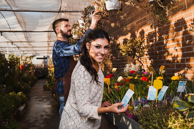 Gens qui prennent soin de fleurs en serre