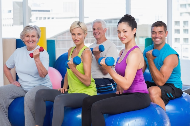 Les gens qui travaillent avec des haltères en cours de gym