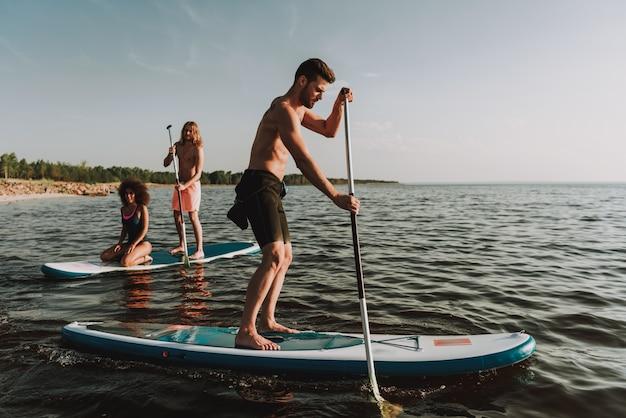 Les gens ramer surfs en mer avec des pagaies.