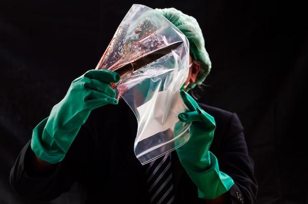 Les gens regardent un couteau des armes et du sang dans un sac en plastique transparent