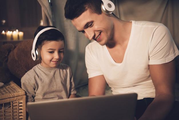 Les gens regardent un film sur un ordinateur portable avec un casque la nuit.