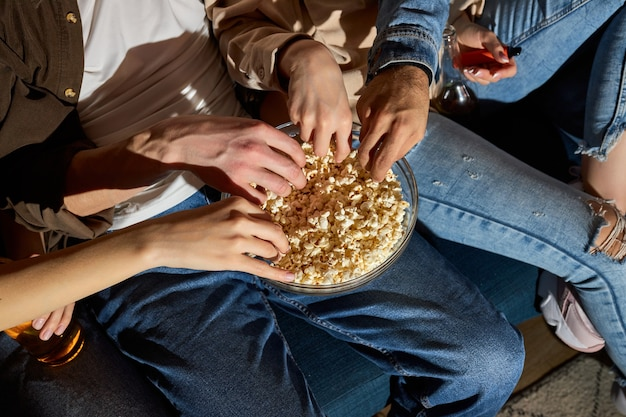Les gens regardent la télévision, une émission de comédie ou un film et mangent une collation de pop-corn, assis sur un canapé confortable à la maison, des amis recadrés profitant du temps libre, le week-end ensemble