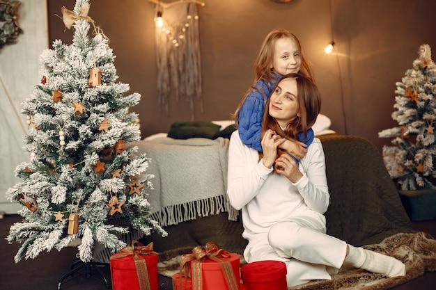 Les gens réparent pour noël. mère jouant avec sa fille. la famille se repose dans une salle de fête. enfant dans un pull bleu.